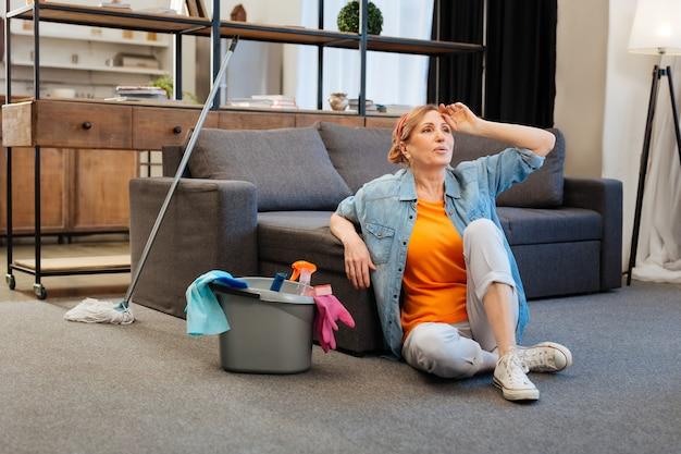 Gelando no chão. mulher de cabelos claros cansada e ansiosa em uma camiseta laranja descansando no chão de carpete
