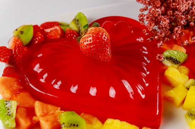 Gelatina de forma de coração decorada com morango fresco, kiwi e abacaxi.