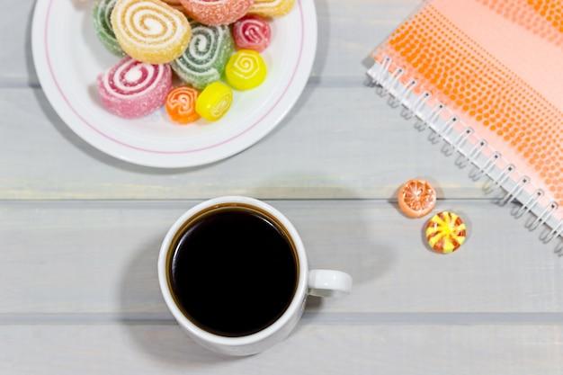 Gelatina de frutas, caderno e uma xícara de café em uma mesa de madeira cinza