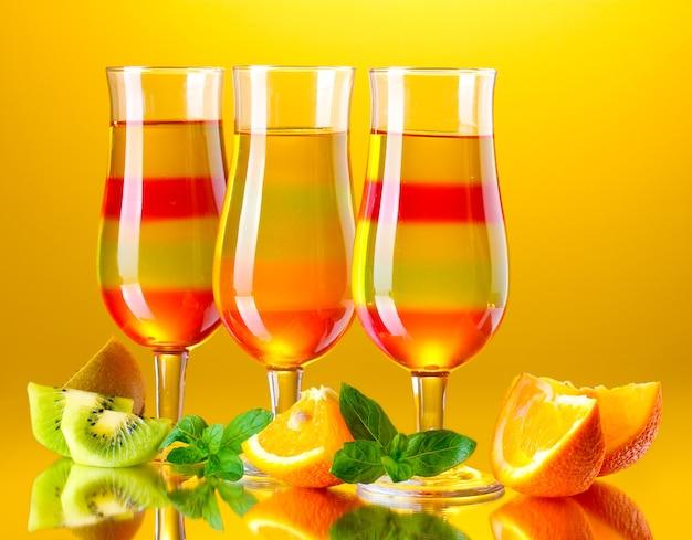 Gelatina de frutas em copos e frutas em amarelo