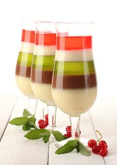 Gelatina de frutas em copos, groselha e hortelã na mesa de madeira