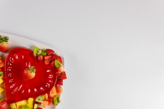 Gelatina de morango em forma de coração com frutas na chapa branca