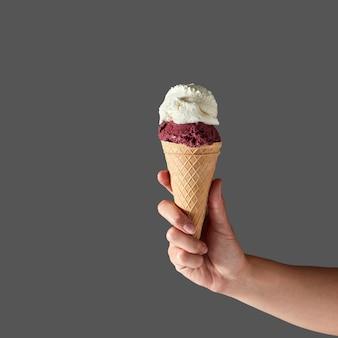 Gelato de frutas vermelhas e sorvete de leite em forma de bola em casquinha de waffle, que é segurada pela mão de uma mulher em uma parede cinza. conceito de verão com espaço de cópia.