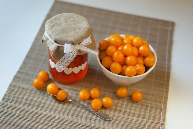 Geléia amarela de ameixa cereja, frutas frescas com vitaminas e frutas vermelhas. marmelada caseira em frasco de vidro marrom