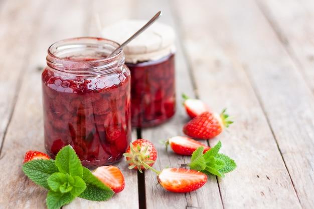 Geléia caseira de srawberry em frasco de vidro na mesa de madeira.