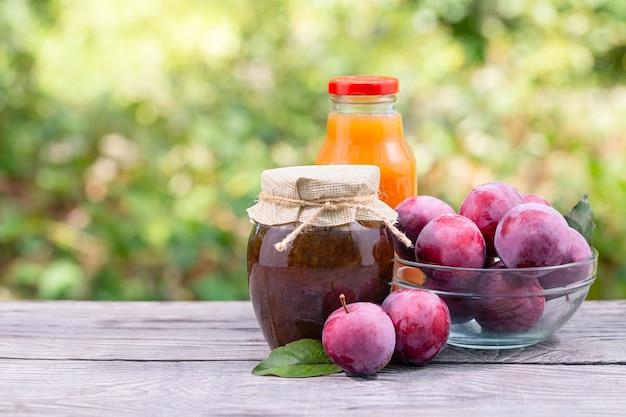 Geléia de ameixa e suco em potes e ameixas na mesa de madeira