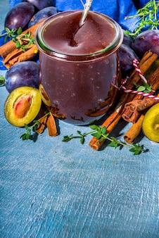 Geleia de ameixa picante de outono em um pequeno frasco, com canela, tomilho, anis e ameixas frescas no fundo azul de concreto.