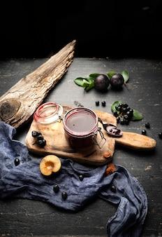 Geléia de ameixa recém-feita em uma jarra e frutas sobre uma mesa com cortinas.