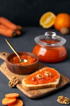 Geléia de cenoura com pão e uma jarra em uma superfície escura