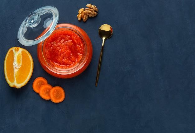 Geléia de cenoura em uma jarra em um fundo azul escuro
