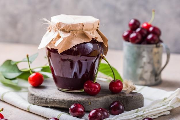 Geléia de cereja agridoce caseira com cerejas frescas na mesa de luz
