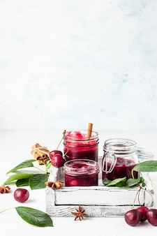 Geléia de cereja caseira com especiarias (canela, anis) com cerejas frescas nos potes em uma pedra clara