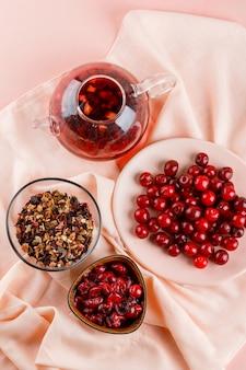 Geléia de cereja com cerejas, chá, ervas secas em uma tigela sobre têxteis e rosa