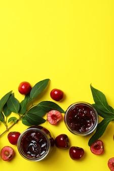 Geléia de cereja e ingredientes em fundo amarelo
