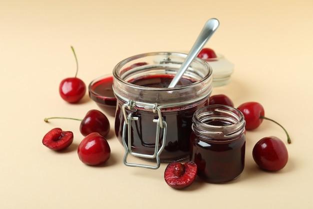 Geléia de cereja e ingredientes em fundo bege