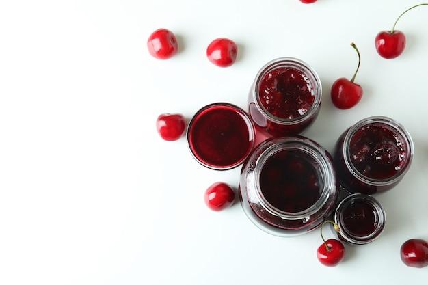 Geléia de cereja e ingredientes em fundo branco