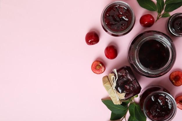 Geléia de cereja e ingredientes em fundo rosa