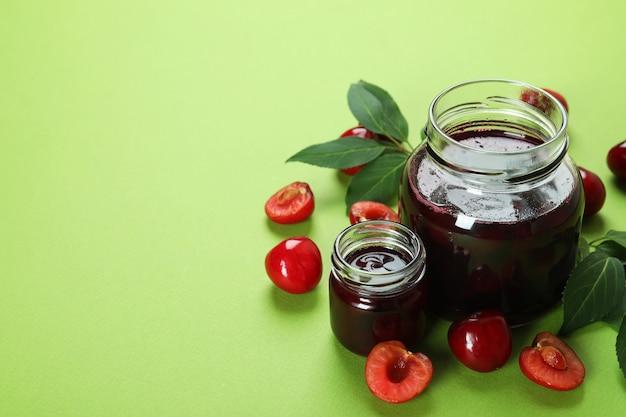 Geléia de cereja e ingredientes em fundo verde