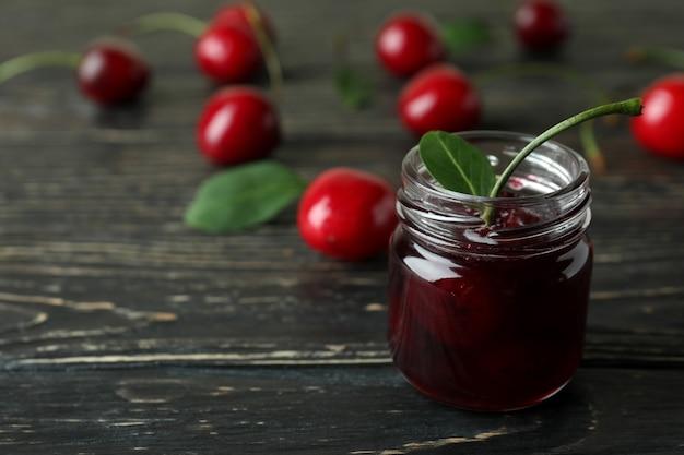 Geléia de cereja e ingredientes em mesa de madeira rústica