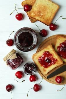 Geléia de cereja e ingredientes na mesa de madeira branca