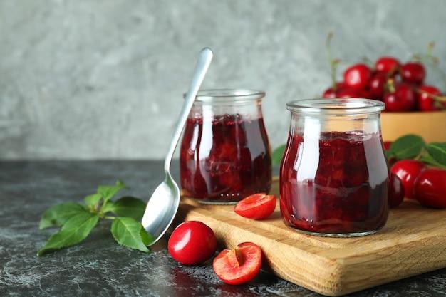 Geléia de cereja e ingredientes na mesa preta esfumada