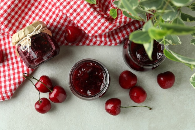 Geléia de cereja e ingredientes na mesa texturizada branca