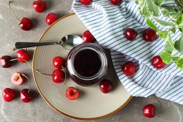 Geléia de cereja e ingredientes na mesa texturizada cinza