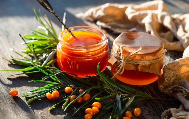 Geleia de espinheiro em potes de vidro, galhos e frutas frescas