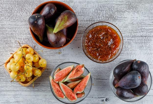 Geléia de figo em uma tigela com figos, cerejas planas leigos em um sujo