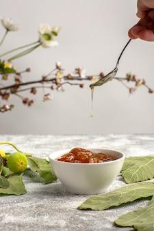 Geleia de figos doces com flores na superfície branca.