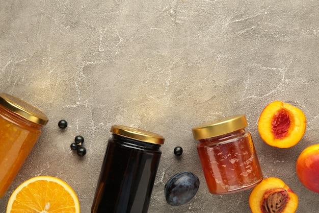 Geléia de fruta caseira na jarra com frutas frescas e bagas em fundo cinza.