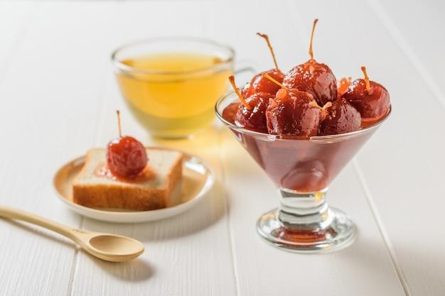 Geléia de frutas vermelhas, pão e chá na mesa branca. doces caseiros de acordo com receitas antigas.