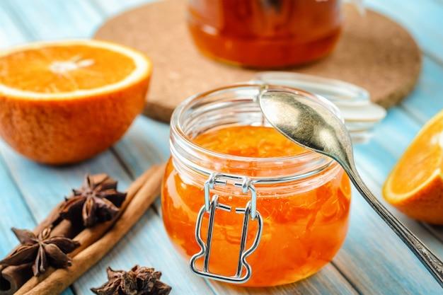 Geléia de laranja em frasco de vidro e ingredientes em fundo azul