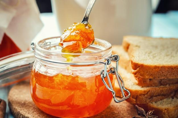 Geléia de laranja em frasco de vidro e pão fatiado