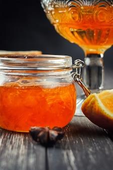 Geléia de laranja em frasco de vidro em madeira