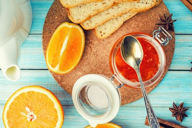 Geléia de laranja em frasco de vidro, torradas e pedaços de laranja sobre fundo azul de madeira