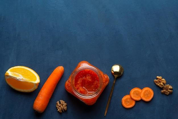 Geléia de legumes de cenoura em uma jarra contra um fundo escuro