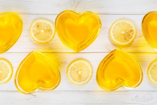 Geléia de limão amarelo no coração em forma de vidro na superfície de madeira branca, vista superior
