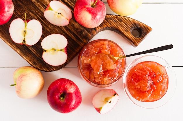 Geléia de maçã perfumada e metades de maçãs em uma placa de madeira e um fundo branco. vista do topo.