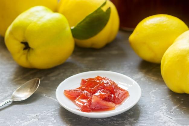 Geléia de marmelo em um pires branco, frutas de marmelo e potes de geléia em um fundo cinza.