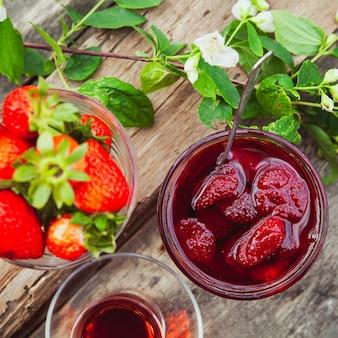 Geléia de morango com colher, chá em vidro, morangos, ramo de flores em um prato na mesa de madeira, plana leigos.