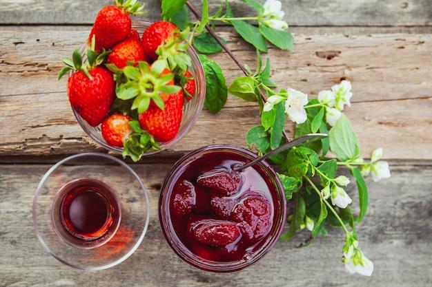 Geléia de morango com colher, chá em vidro, morangos, ramo de flores em um prato na mesa de madeira, vista superior.