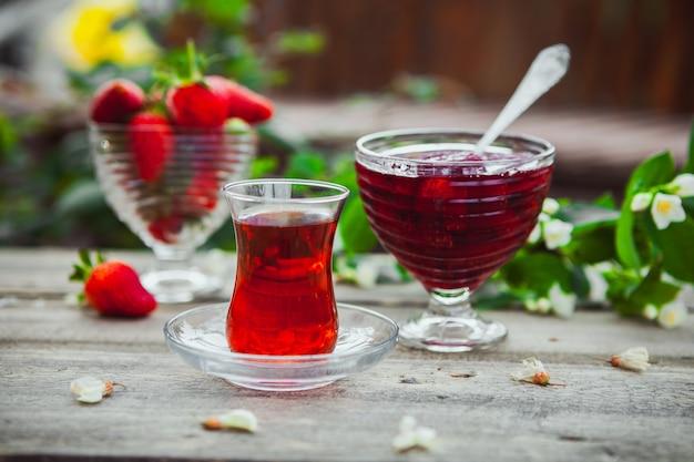 Geléia de morango com flores no galho, um copo de chá, colher, morangos em um prato na mesa de madeira e quintal, vista lateral.