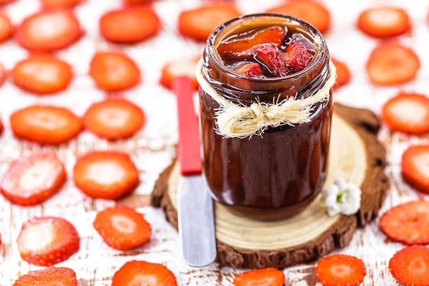 Geléia de morango com pedaços de frutas, morangos fatiados na superfície
