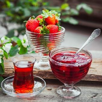 Geléia de morango em um prato com colher, chá em copo, morangos, planta close-up na mesa de madeira e quintal