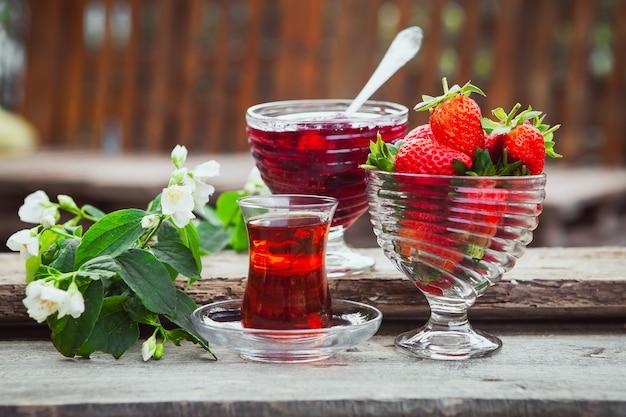 Geléia de morango em um prato com colher, chá em copo, morangos, vista lateral para o ramo de flores na mesa de madeira e quintal
