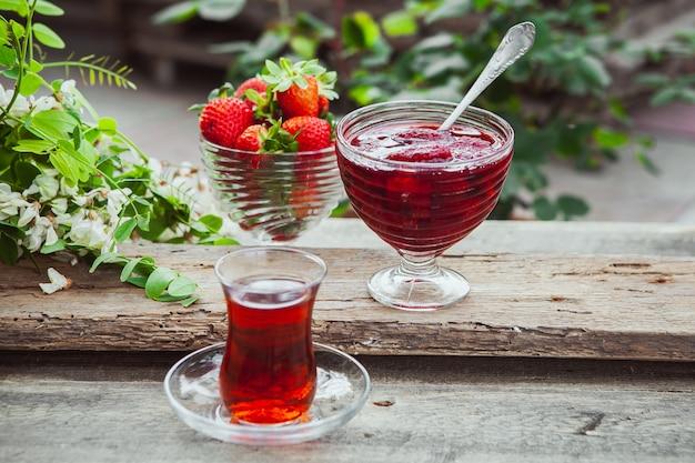 Geléia de morango em um prato com colher, um copo de chá, morangos, planta vista superior na mesa de madeira e calçada