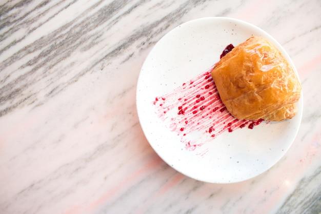 Geléia de morango no pão croissant no prato pronto para servir