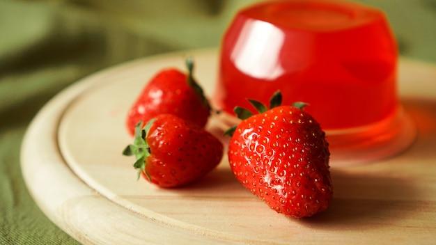 Geléia de morango vermelha com frutas vermelhas em um recipiente de plástico