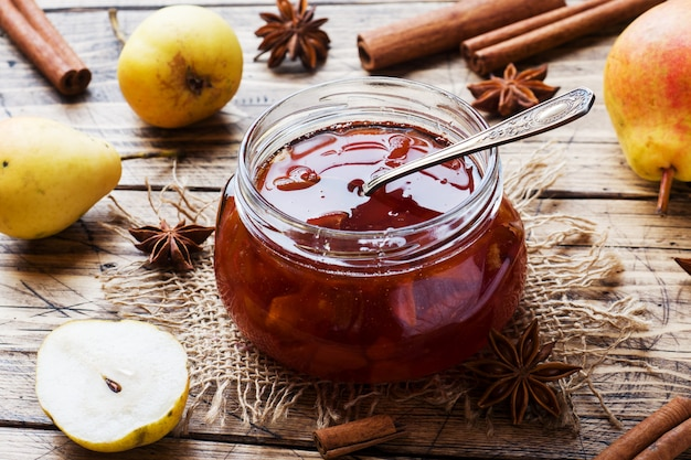 Geléia de pêra caseira em uma jarra e peras frescas